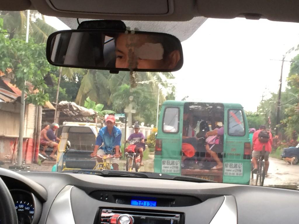 Blick aus dem Auto: Tricycle und Motorrad von vorn; grüner Jeepney und Fahrrad von hinten