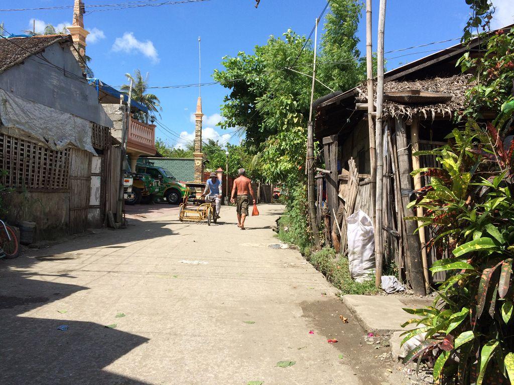 Ein Weg zwischen Häusern und Hütten - auf dem Rückweg vom Großmarkt (in Oton, in der Provinz Iloilo, auf der Insel Panay, die zu der Inselgruppe der Visayas gehört)