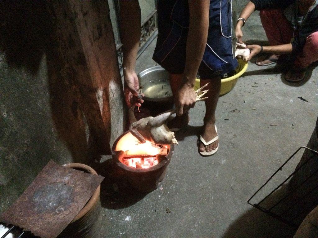 Die Jungs beim (frischen) Hühnchen braten - getötet, gerupft und über den Feuertopf gehalten